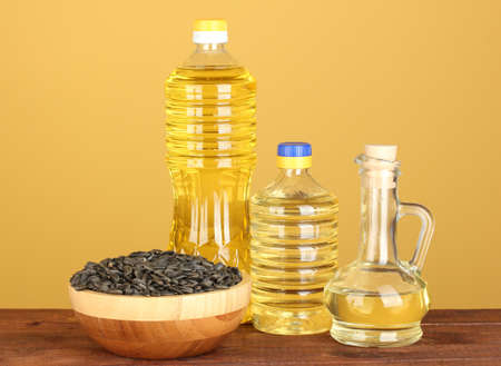 sunflower oil in bottles on yellow background close-up photo
