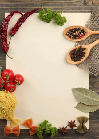 cooking recipe: paper for recipes vegetables, and spices on wooden table