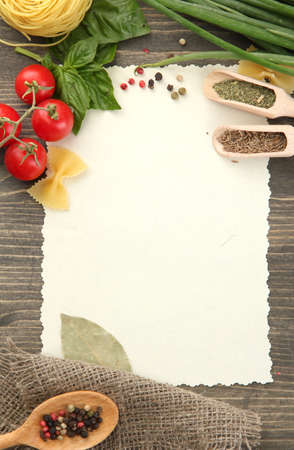 recipe: paper for recipes vegetables, and spices on wooden table