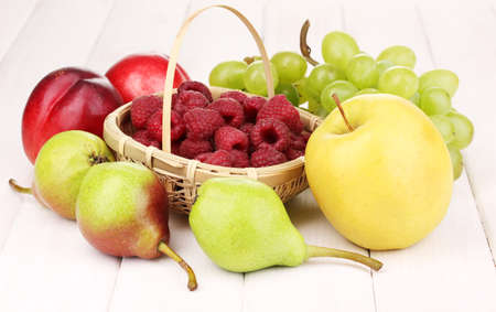 ripe sweet fruits and berries on wooden background photo
