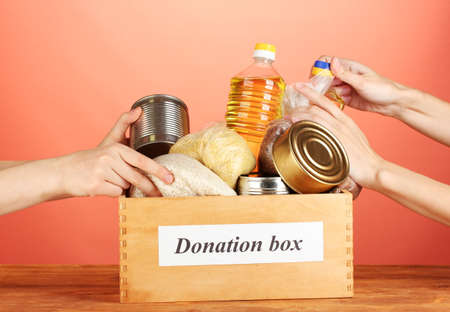 Donation box with food on red background close-up Stock Photo - 14707866