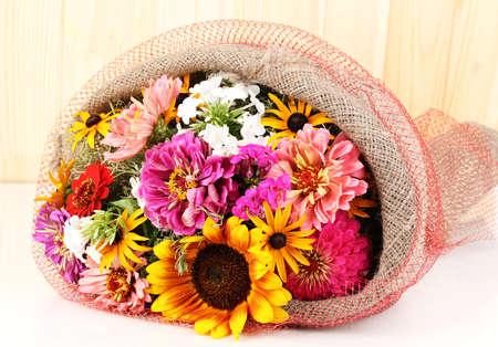 Hermoso ramo de flores de colores brillantes en tela de saco en el fondo de madera Foto de archivo - 14708129