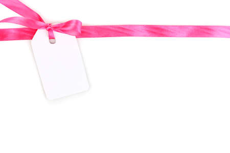 winter gift: Blank gift tag with pink satin bow and ribbon isolated on white