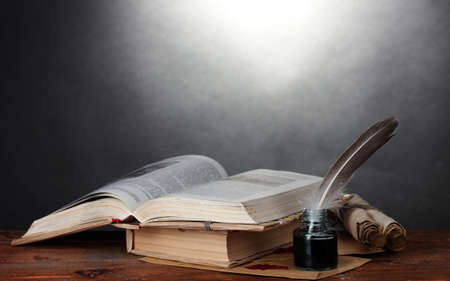 old book: old books, scrolls, feather pen and inkwell on wooden table on grey background Stock Photo