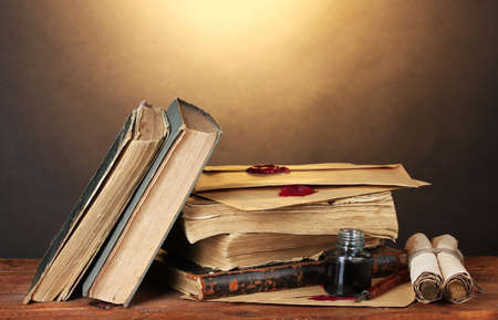 ged: old books, scrolls, ink pen and inkwell on wooden table on brown background