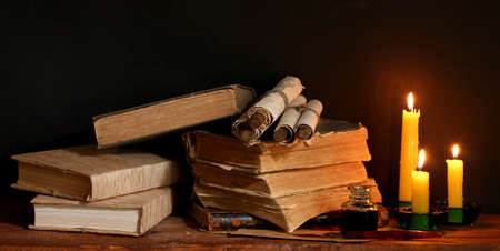 ged: old books, scrolls, ink pen inkwell and candles on wooden table on brown background