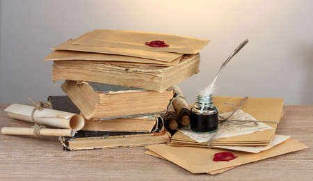 ged: old books, scrolls, feather pen and inkwell on wooden table on grey background Stock Photo