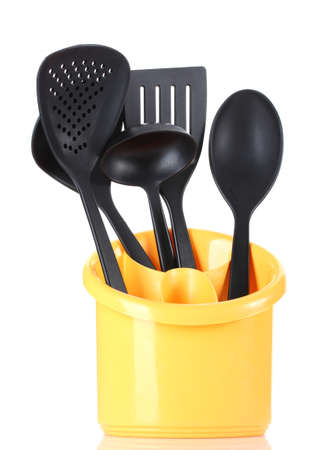 black kitchen utensils in yellow stand isolated on white photo