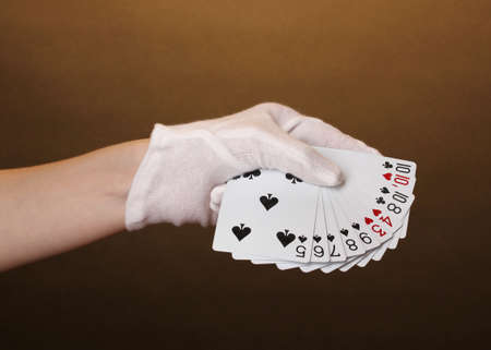 lear: Cards in hand on brown background