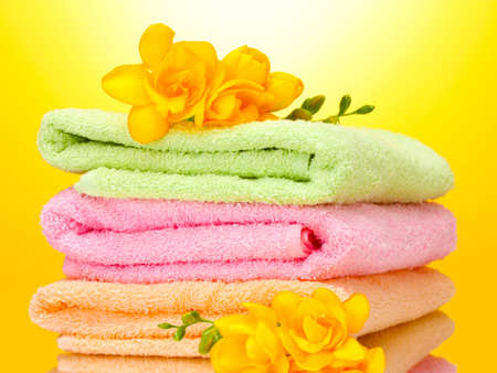bathroom design: colorful towels and flowers on yellow background