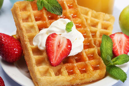 belgium waffles with honey, strawberries and mint on plate isolated on white photo