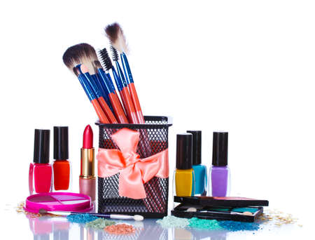 make-up brushes in holder and cosmetics isolated on white photo