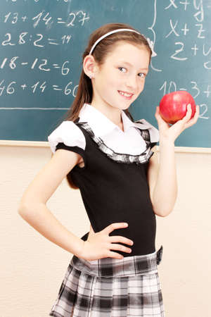 beautiful little girl in school uniform with apple in class room photo