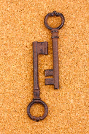 Two antique keys on cork background photo