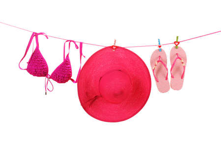 Women's bra swimsuit, hat and flip-flops hanging on a rope on white background photo