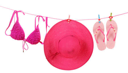 Womens bra swimsuit, hat and flip-flops hanging on a rope on white background photo