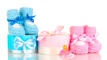 shoe boxes: baby boots, pacifier, gifts and blank postcard  isolated on white