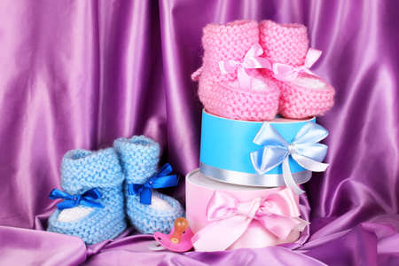 pink and blue baby boots, pacifier and gifts on silk background  photo