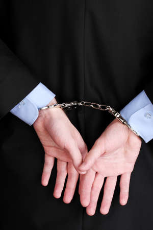 Businessman hands fettered with handcuffs photo