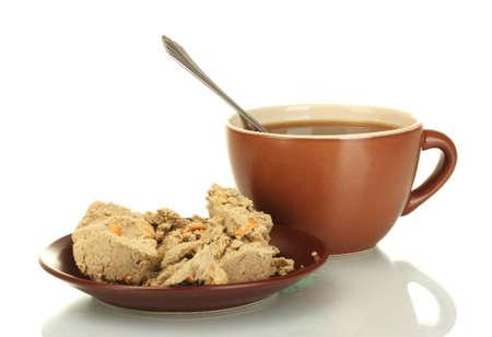 confect: Una tazza di t� e piattino con deliziosi halva isolato su bianco