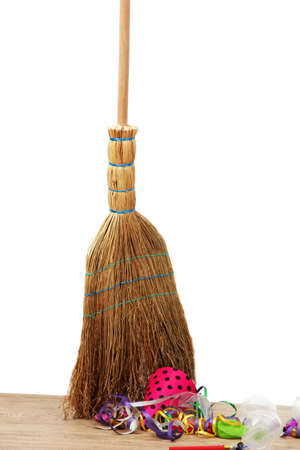 Broom sweep the trash after a party on white background close-up photo