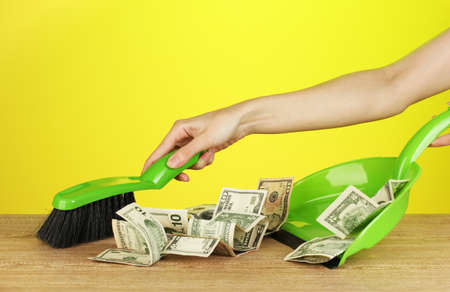 sweeps: Sweeps money in the shovel on colorful background close-up Stock Photo