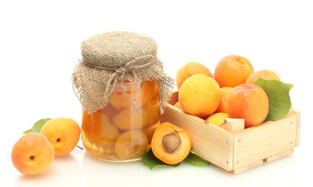 canned apricots in a jar and fresh apricots in wooden box isolated on white photo