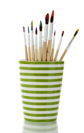 Paint brushes with gouache in cup isolated on white photo