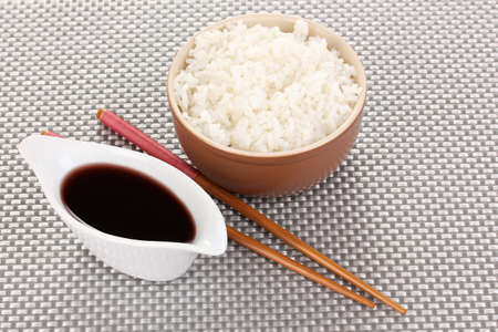 Bowl of rice and chopsticks on grey mat photo