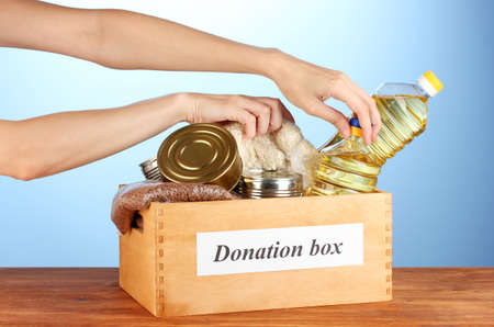 Donation box with food on blue background close-up Stock Photo - 14709447