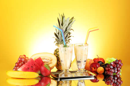 pineapple  glass: Milk shakes with fruit on yellow background close-up Stock Photo