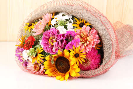 ronantic: Beautiful bouquet of bright flowers in sacking on wooden background