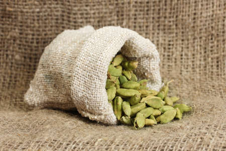 Green cardamom in sack on canvas background close-up photo