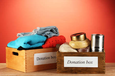 Donation boxes with clothing and food on red background close-up photo