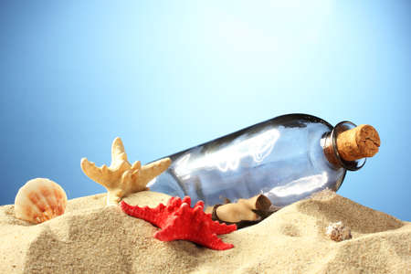 Glass bottle with note inside on sand, on blue background Stock Photo - 14712963