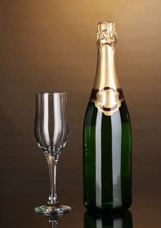 Bottle of champagne and goblet on brown background photo