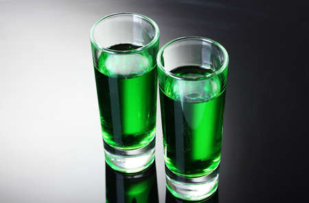 intoxicate: Two glasses of absinthe on grey background