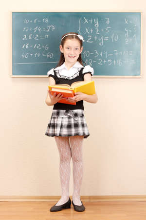 beautiful little girl in school uniform with books in class room Stock Photo