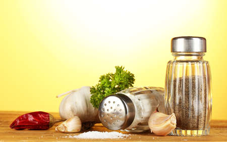 salt and pepper: Salt and pepper mills, garlic and parsley on wooden table on yellow background