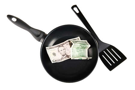 Banknotes in a frying pan with cooking spatula isolated on white photo