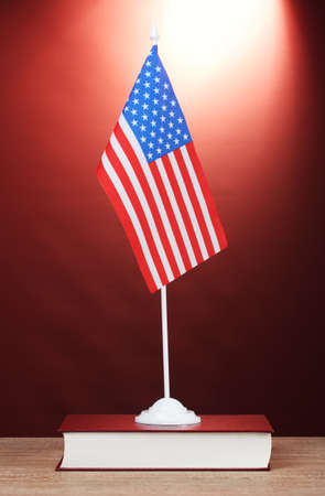 American flag on the stand and book on wooden table on red background photo