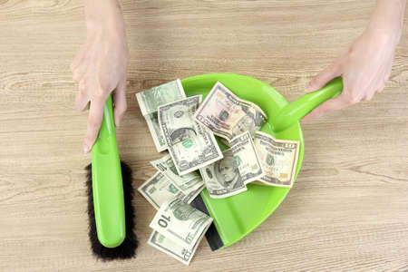 waterfall  dirty: Sweeps money in the shovel on wooden background close-up Stock Photo