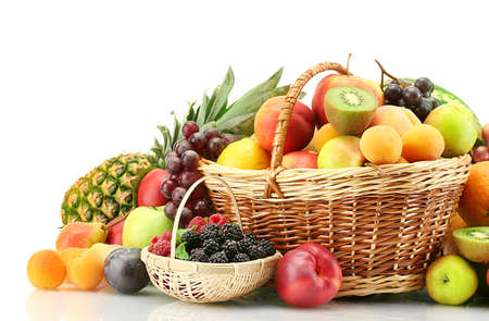 Assortment of exotic fruits and berries in baskets isolated on white photo