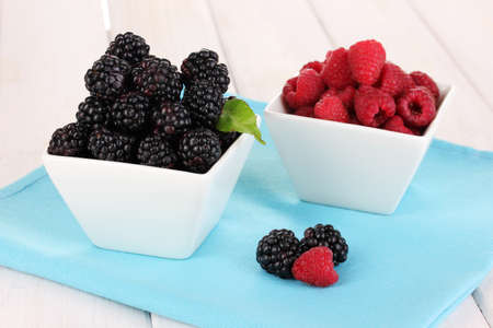 Ripe raspberries and brambles on wooden table photo