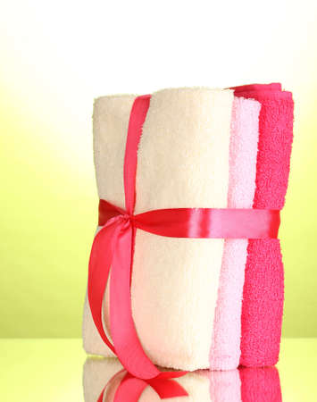 Colorful towels with ribbon on green background Stock Photo - 14735784
