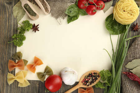 paper for recipes vegetables, and spices on wooden table photo