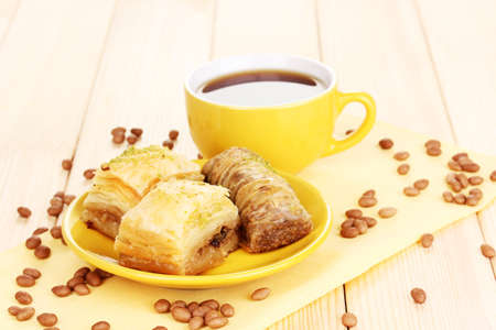 Sweet baklava on plate with tea on wooden background photo
