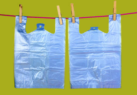 Cellophane bags hanging on rope on green background photo