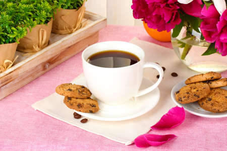 cup of coffee, cookies, orange and flowers on table in cafe photo