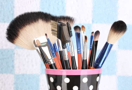 Makeup brushes in a black polka-dot cup on colorful background close-up photo